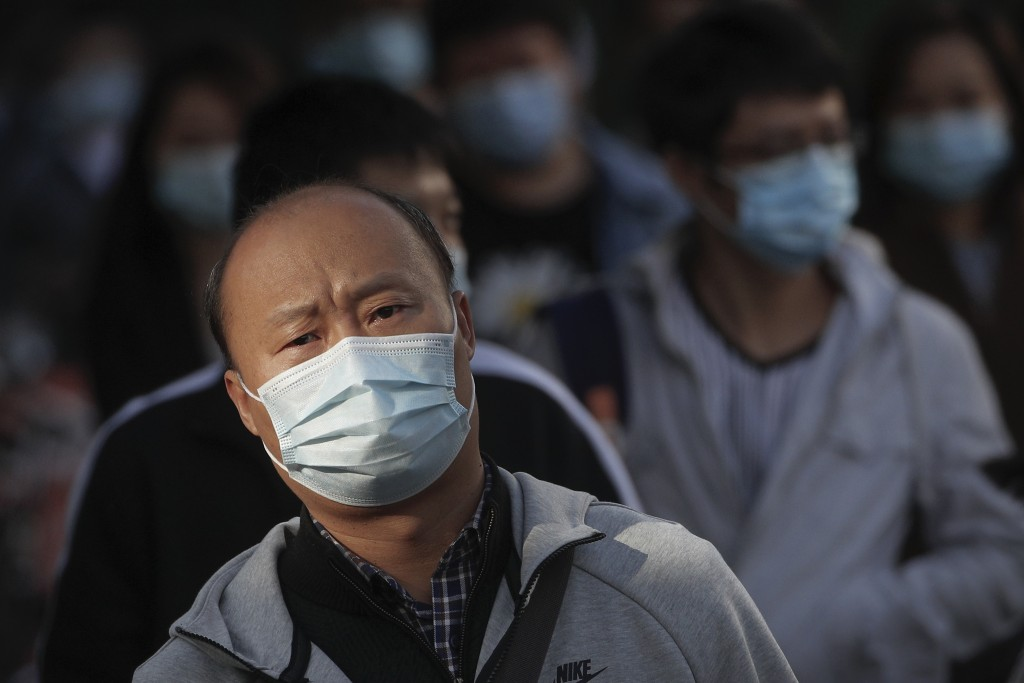 People wearing face masks to help curb the spread of the coronavirus walk on a street during the morning rush hour in Beijing, Tuesday, Oct. 13, 2020....