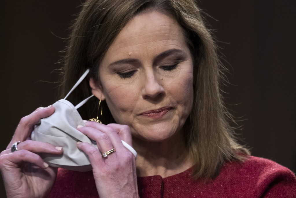 Supreme Court nominee Amy Coney Barrett removes her facemask as she arrives for the second day of her confirmation hearing before the Senate Judiciary...