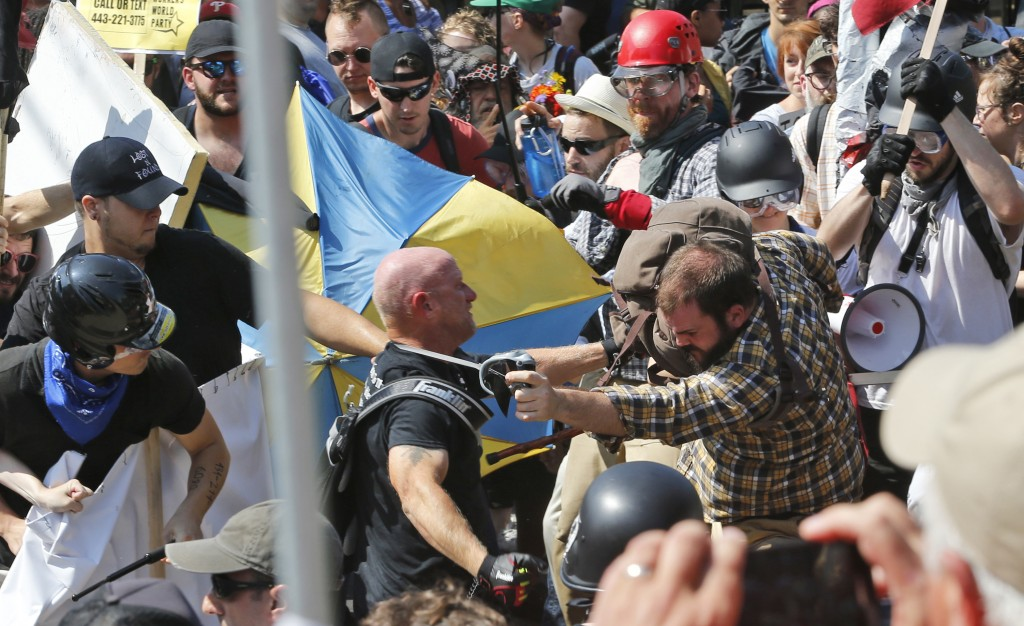 FILE - In this Aug. 12, 2017 file photo, white nationalist demonstrators clash with counter demonstrators at the entrance to Lee Park in Charlottesvil...