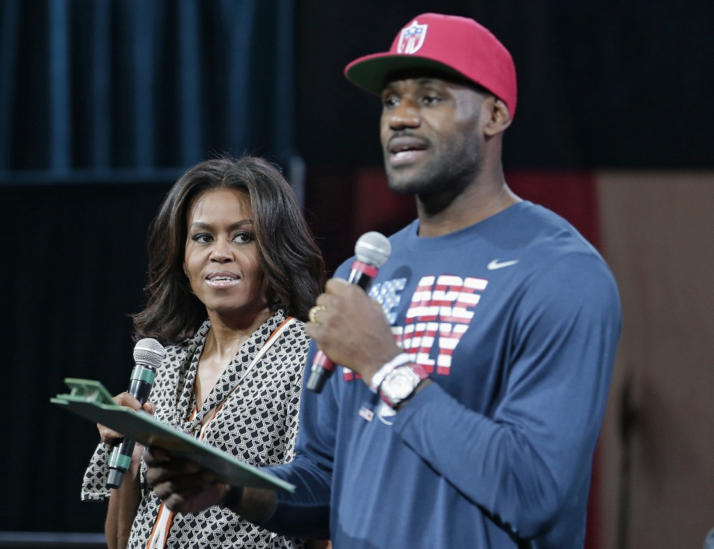 FILE - In this Oct. 21, 2015, file photo, former first lady Michelle Obama looks on as NBA star LeBron James speaks at The University of Akron, in Akr...