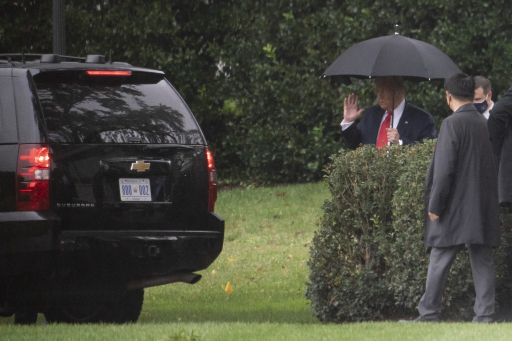 President Donald Trump holds an umbrella as he walks to his car on the South Lawn of the White House Monday, Oct. 12, 2020, in Washington. Trump is en...