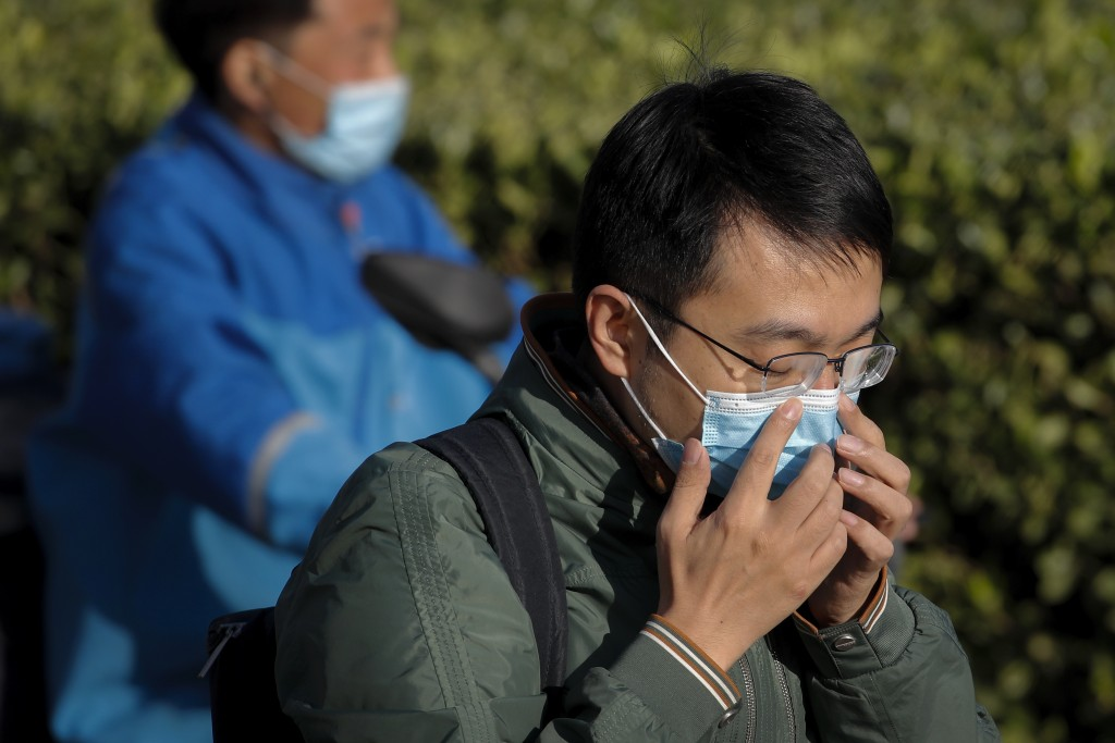 A man adjusts his face mask to help curb the spread of the coronavirus on a street during the morning rush hour in Beijing, Tuesday, Oct. 13, 2020. (A...