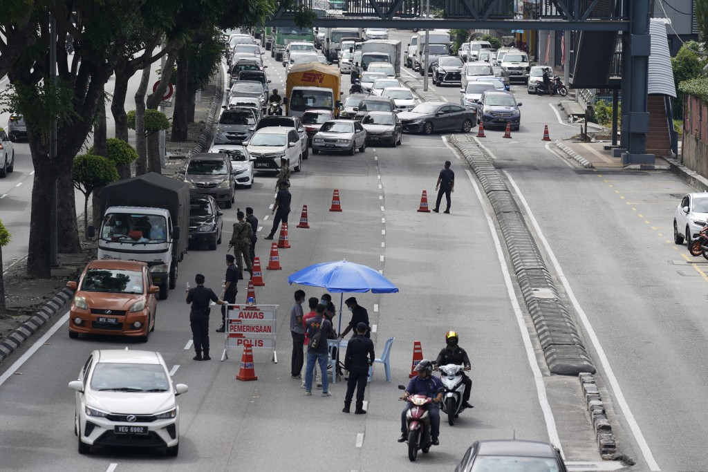 Police officers check vehicles at a roadblock to ensure that people abide by a movement control order in downtown Kuala Lumpur, Malaysia, Wednesday, O...