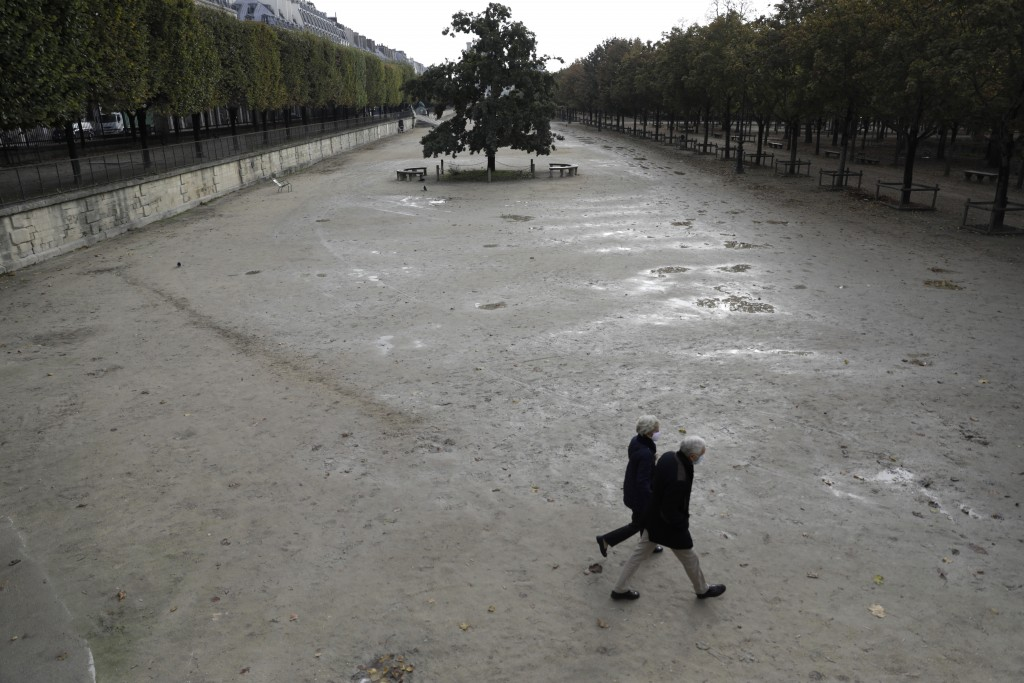 People walk in the empty Tuileries gardens Wednesday, Oct.14, 2020 in Paris. French President Emmanuel Macron is giving a nationally televised intervi...