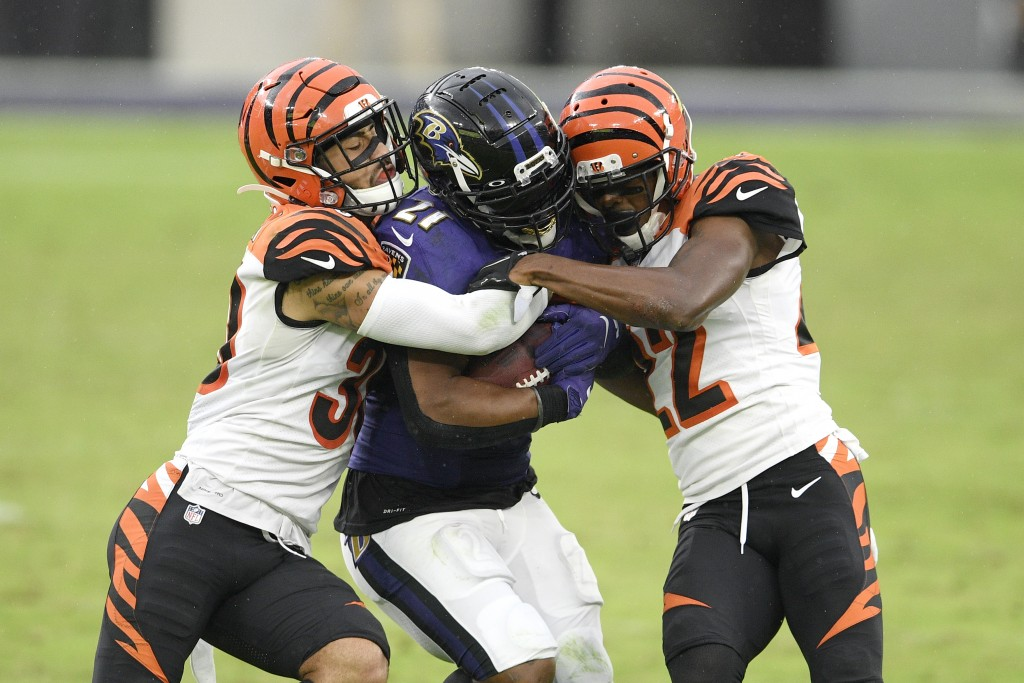 Baltimore Ravens running back Mark Ingram, center, is hit by Cincinnati Bengals free safety Jessie Bates, left, and cornerback William Jackson during ...