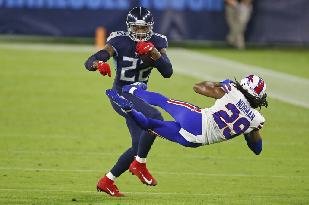 Tennessee Titans running back Derrick Henry (22) knocks down Buffalo Bills cornerback Josh Norman (29) in the first half of an NFL football game Tuesd...