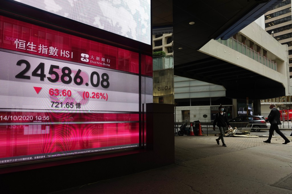 People walk past a bank's electronic board showing the Hong Kong share index at Hong Kong Stock Exchange Wednesday, Oct. 14, 2020. Shares were mostly ...