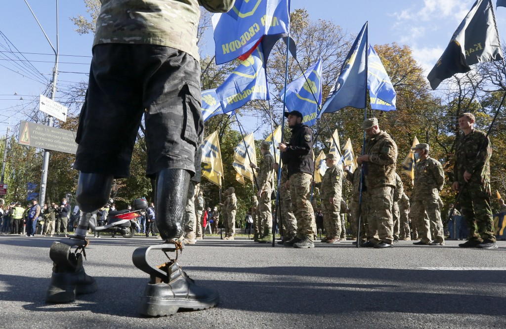 A handicapped Ukrainian army veteran watches a a rally marking Defender of Ukraine Day in centre Kyiv, Ukraine, Wednesday, Oct. 14, 2020. (AP Photo/Ef...