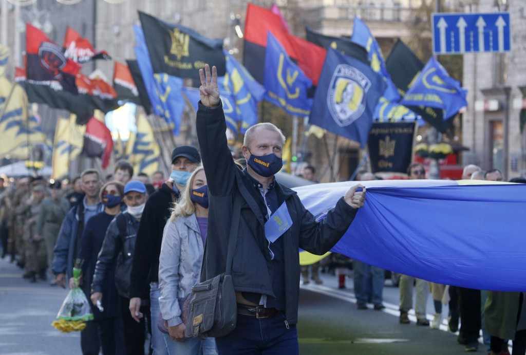 People carry the Ukrainian National flag at a rally marking Defender of Ukraine Day in centre Kyiv, Ukraine, Wednesday, Oct. 14, 2020. (AP Photo/Efrem...