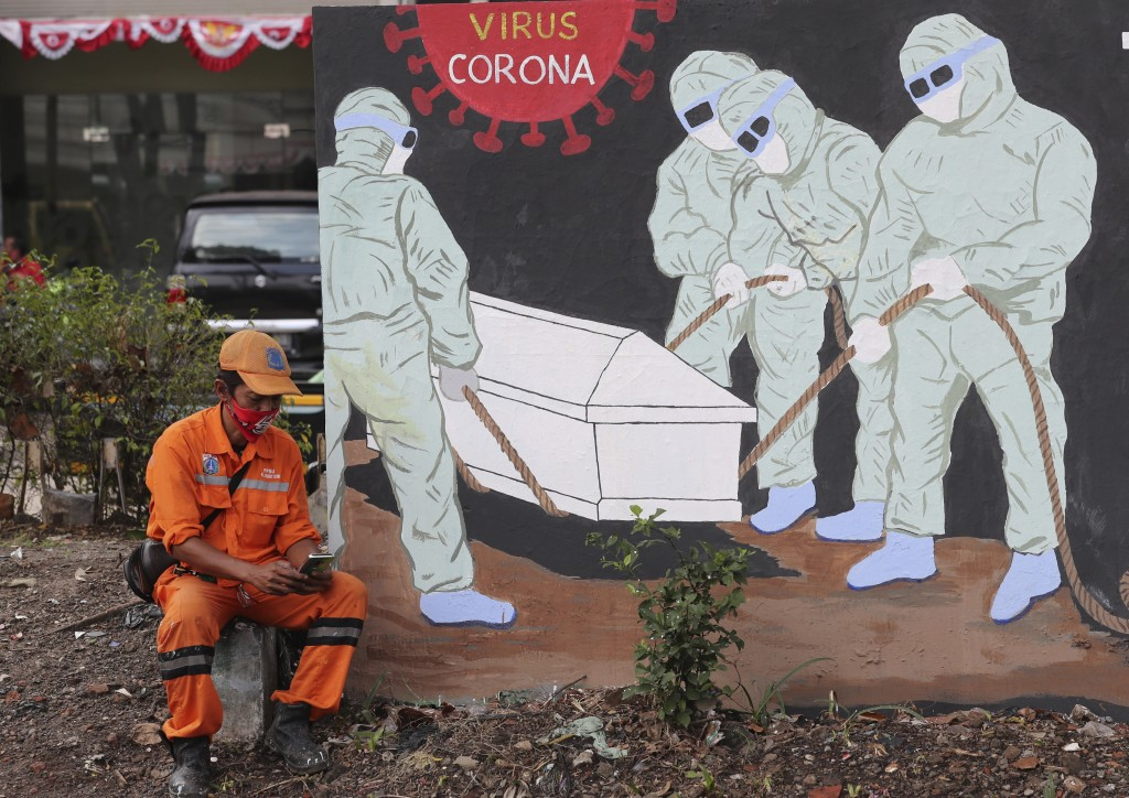 Street sweeper checks his mobile phone as he takes a break near a coronavirus-themed mural in Jakarta, Indonesia.