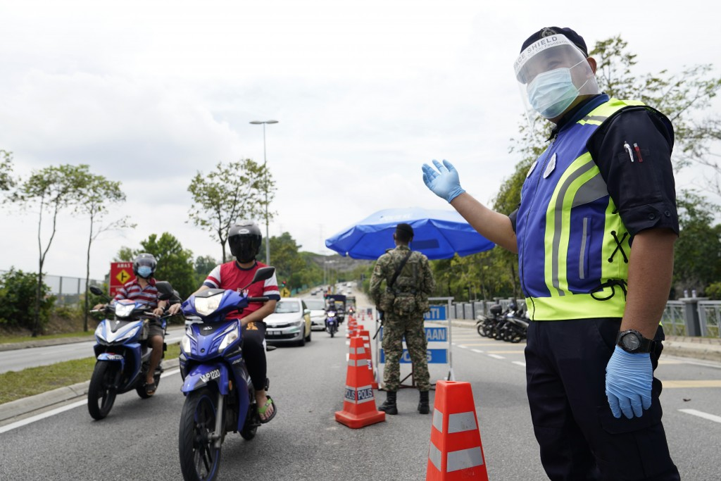 Police officers check vehicles at a roadblock to ensure that people abide by a movement control order on the outskirts of Kuala Lumpur, Malaysia, Wedn...