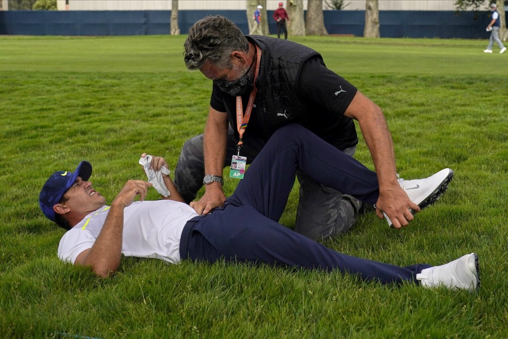 File-This Aug. 7, 2020, file photo shows Brooks Koepka getting treated for an injury on the 12th hole during the second round of the PGA Championship ...