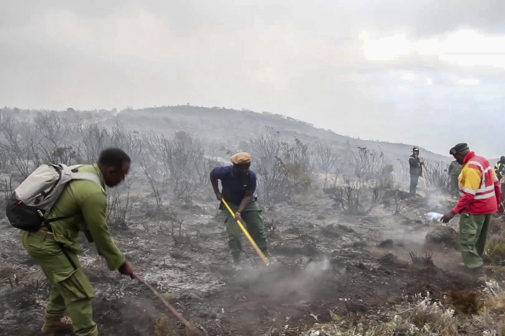 In this image made from video, rangers and volunteers help to put out fires on Mount Kilimanjaro in Tanzania on Monday, Oct. 12, 2020. Tanzanian autho...