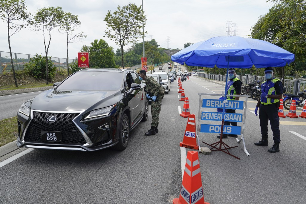 Police officers check vehicles at roadblock to ensure that people abide by the movement control order on the outskirts of Kuala Lumpur, Malaysia, Wedn...