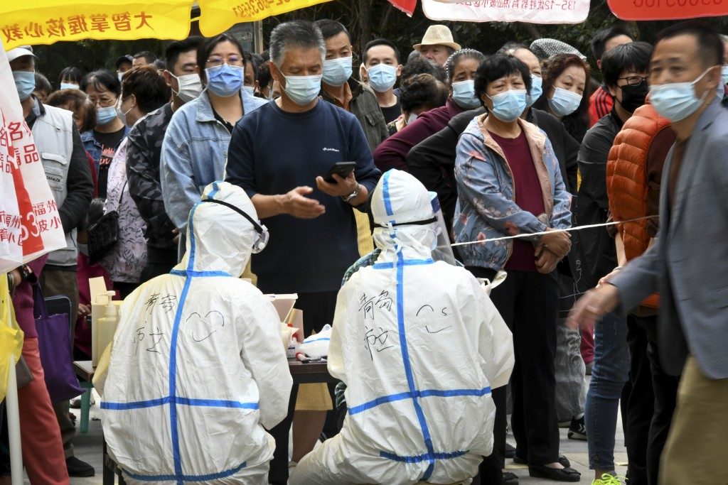 In this photo released by Xinhua News Agency, residents wearing face masks to help curb the spread of the coronavirus line up for the COVID-19 test ne...