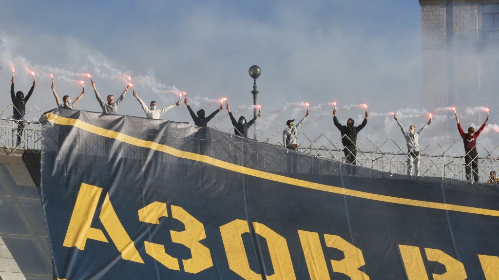 Activists of Ukrainian right-wing paramilitary Azov National Corps light flares as they cheers participants of a rally marking Defender of Ukraine Day...