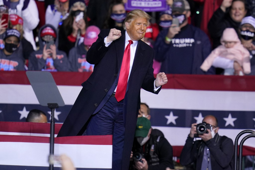 President Donald Trump moves to the song YMCA as he finishes a campaign rally at John P. Murtha Johnstown-Cambria County Airport in Johnstown, Pa., Tu...