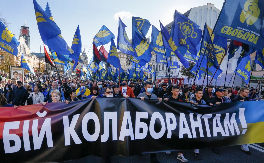 """People carry flags of right-wing party Svoboda and a banner reading """"Fight to collaborators!"""" during a rally marking Defender of Ukraine Day in centre..."""