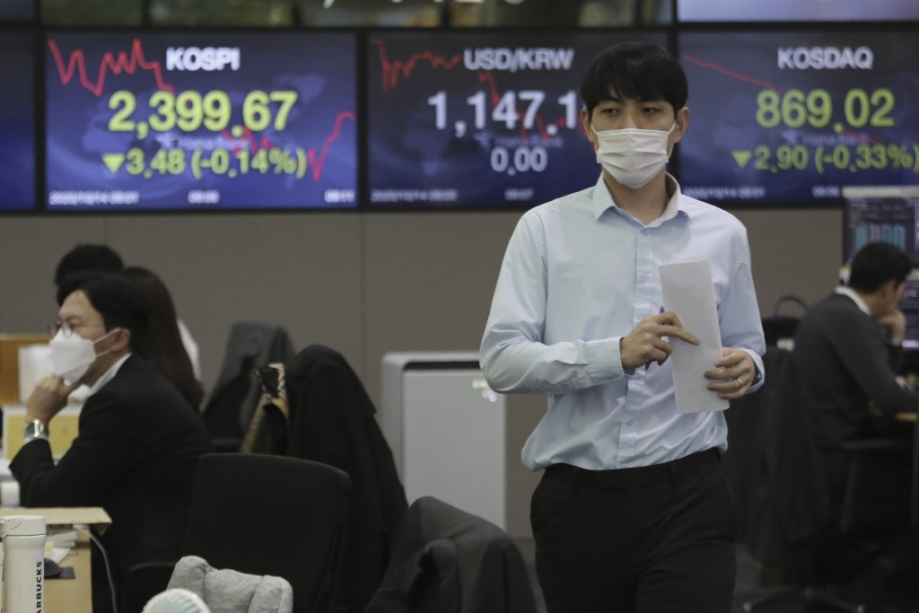 A currency trader walks with documents at the foreign exchange dealing room of the KEB Hana Bank headquarters in Seoul, South Korea, Wednesday, Oct. 1...
