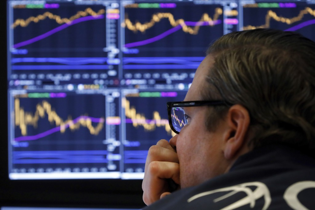 FILE - In this Tuesday, Jan. 28, 2020, file photo, specialist Gregg Maloney watches the screens at his post on the floor of the New York Stock Exchang...