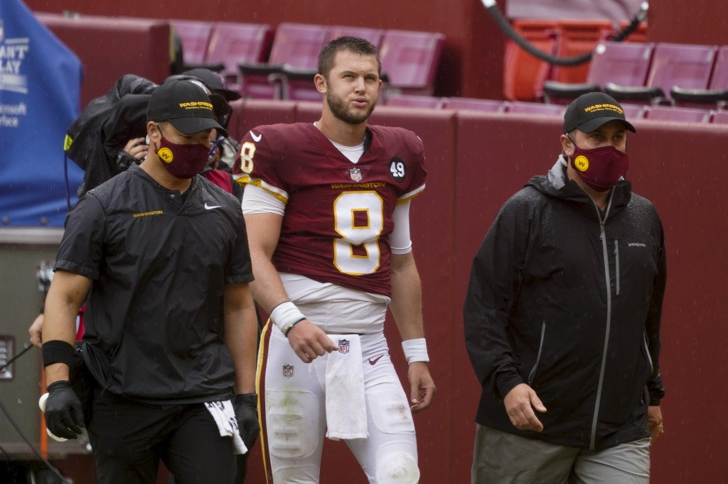 Washington Football Team's Kyle Allen is taken to the locker room after being injured during the first half of an NFL football game against the Los An...