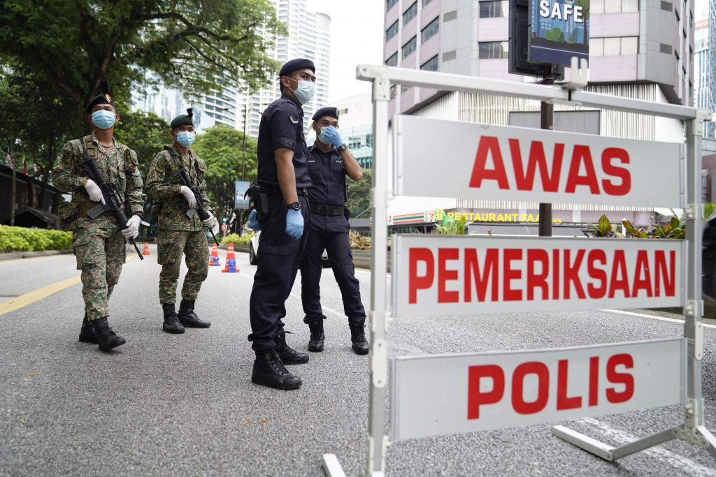 Police and army officers check vehicles at a roadblock to ensure that people abide by a movement control order in downtown Kuala Lumpur, Malaysia, Wed...