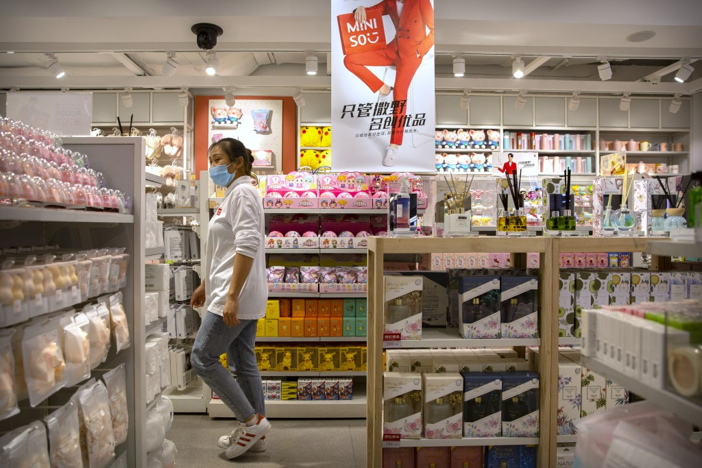 A worker wearing a face mask to protect against the coronavirus walks through a Miniso shop at a shopping mall in Beijing, Thursday, Oct. 15, 2020.  M...