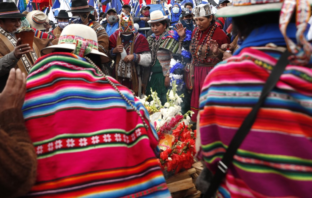 """Supporters of presidential candidate Luis Arce from the Movement Towards Socialism Party, MAS, surround an offering to the """"Pachamama,"""" or Mother Eart..."""