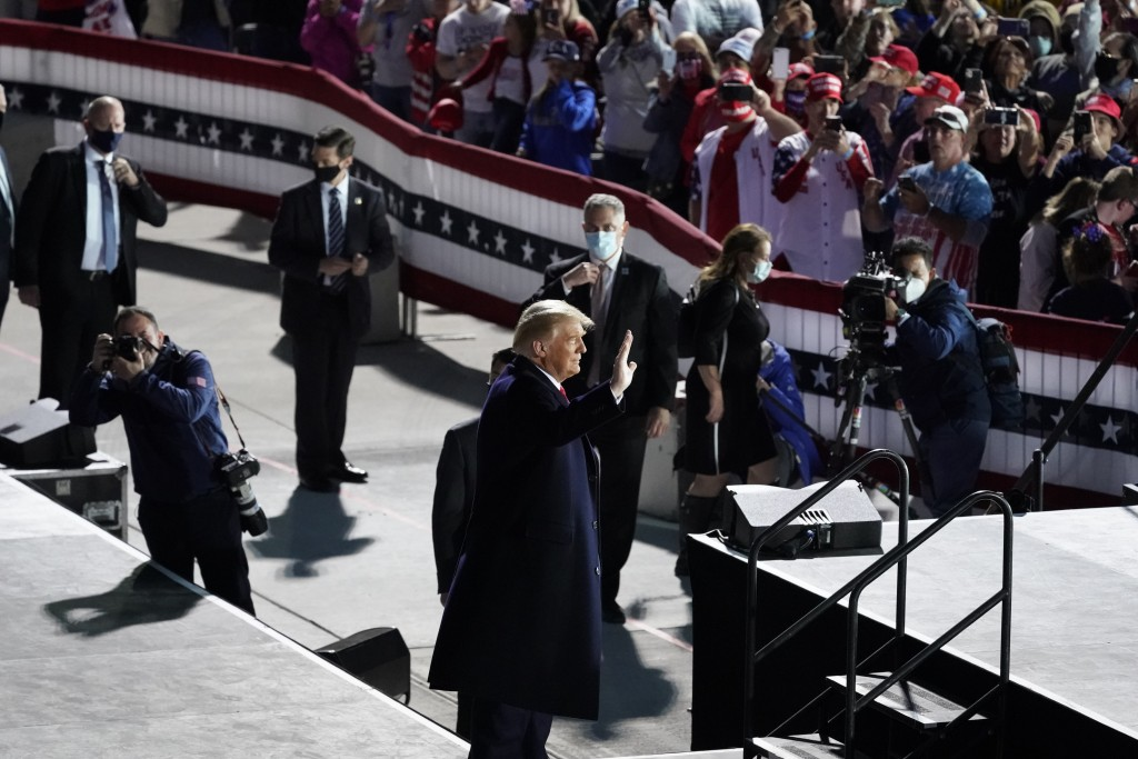 President Donald Trump waves to supporters as he arrives at a campaign rally at Des Moines International Airport, Wednesday, Oct. 14, 2020, in Des Moi...