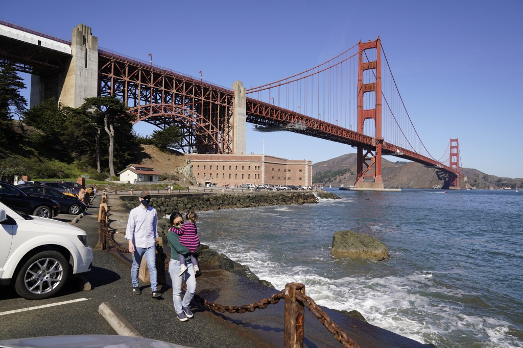 On a clear day people walk along a seawall with Fort Point and the Golden Gate Bridge in the background in San Francisco on Oct. 11, 2020. Wildfires t...