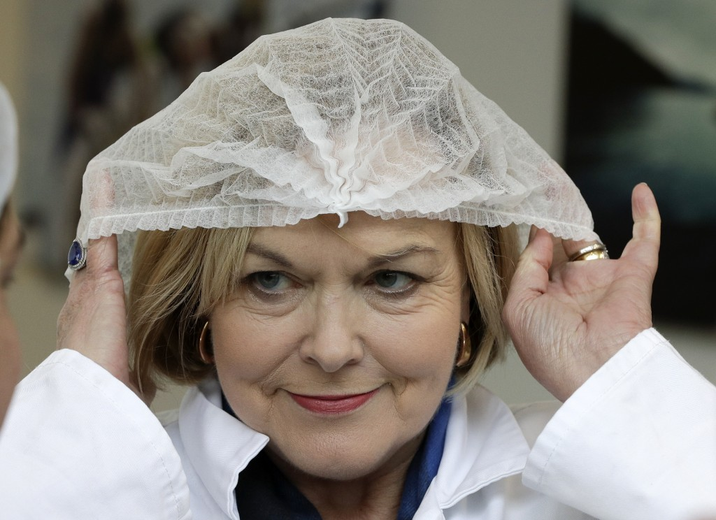 FILE - In this July 30, 2020, file photo, leader of the New Zealand opposition National Party Judith Collins puts on a hairnet before entering a salmo...