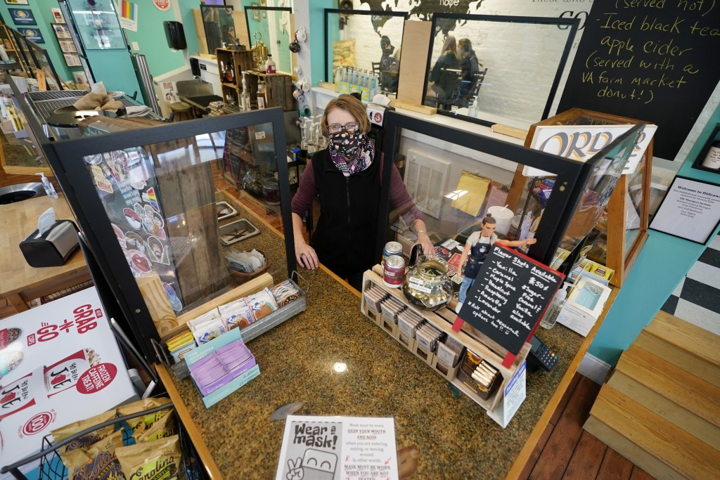 Victoria Leigh Kidd, owner of Hideaway Café, greets customers from behind protective shields in her shop in the Old Town area of Winchester, Va., Wedn...