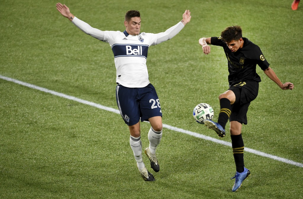 Los Angeles FC forward Christian Torres, right, kicks the ball as Vancouver Whitecaps defender Jake Nerwinski, left, defends during the first half of ...