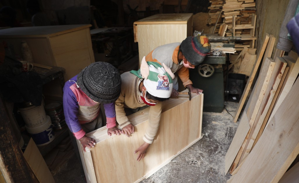 Three of the Delgado children, from right, Yuri, 11, Wendi, 9, and Alison, 8, make a drawer in the family carpentry workshop in El Alto, Bolivia, Wedn...