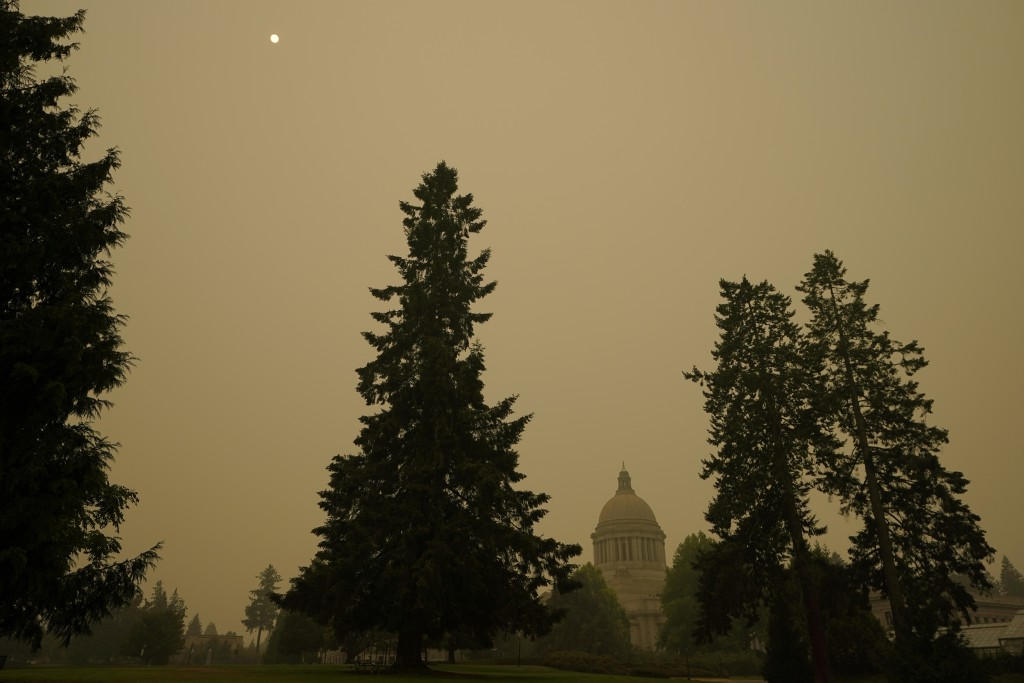 FILE - In this Sept. 12, 2020, file photo, smoke from wildfires in Oregon and California create hazy skies as the sun is seen above the Washington sta...