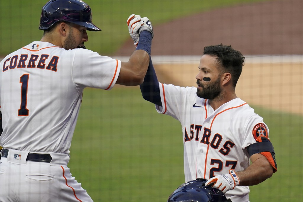 Houston Astros' Jose Altuve is congratulated by Carlos Correa after hitting a solo home run against Tampa Bay Rays pitcher Tyler Glasnow during the fi...