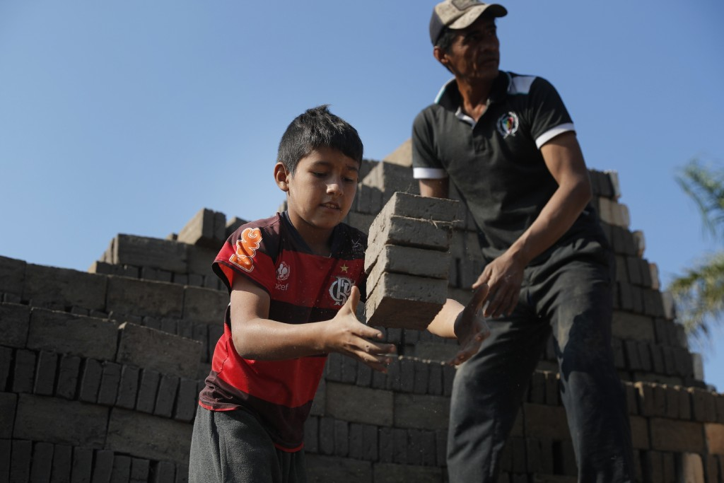 Alejandro, 9, catches bricks to pass over to a man who puts them in the kiln at a brick factory run by his uncles in Tobati, Paraguay, Monday, Aug. 31...