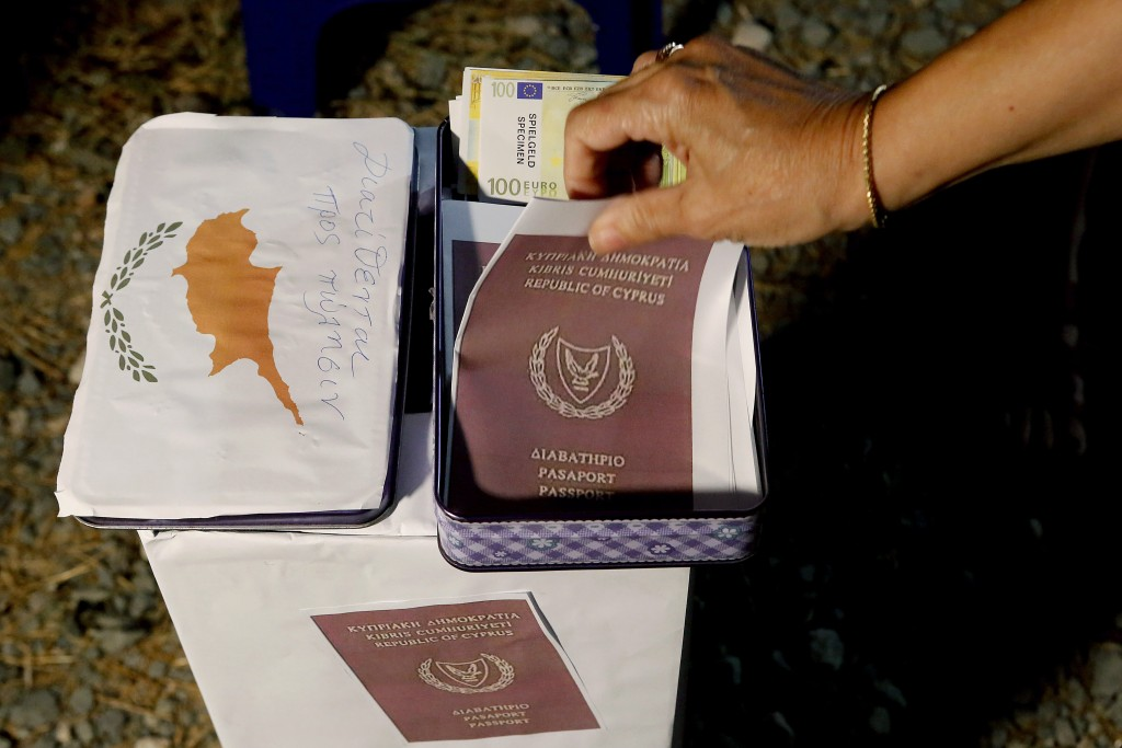 A demonstrator takes a  mock copy of Cyprus passport during a demonstration against corruption outside of the conference center in the capital Nicosia...