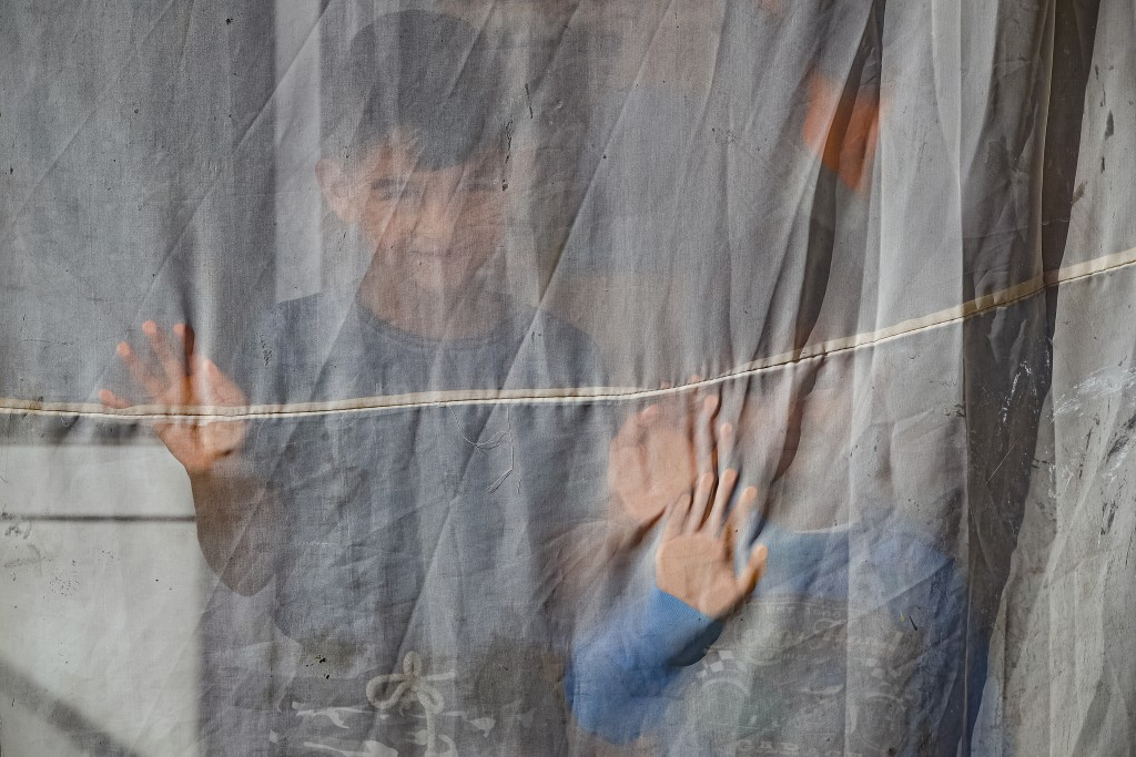 Two young children, nephews of Azime Ali Topchu, 48, playfully pose for a photograph behind a curtain in a village on the outskirts of Burgas, Bulgari...