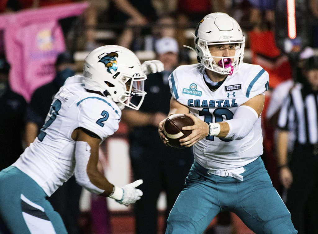 Coastal Carolina quarterback Grayson McCall (10) hands off the football to running back Reese White (2) during the first half of an NCAA football game...