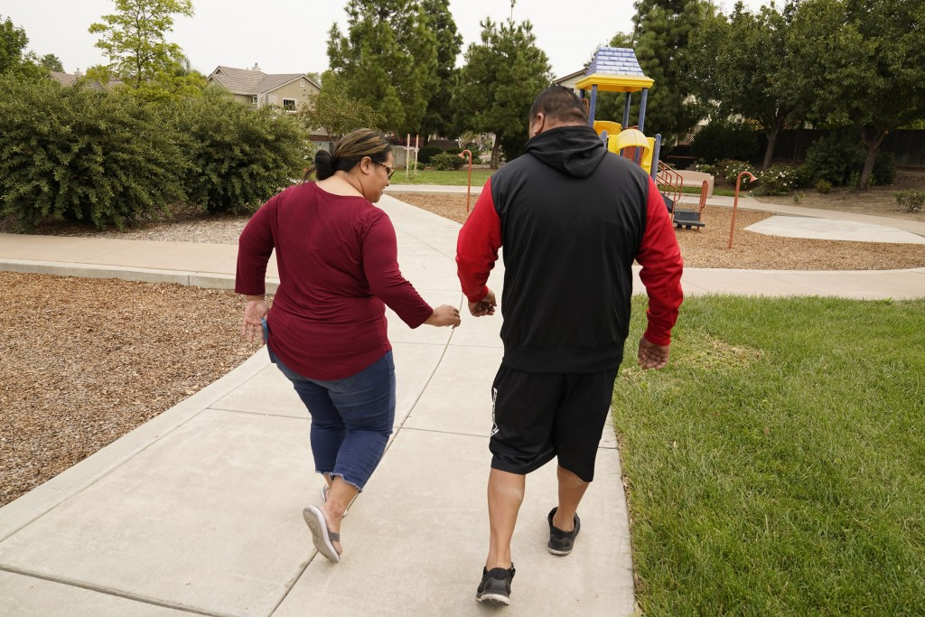 Makerita Iosefo-Va'a and her husband Shaun Va'a walk together in a park near a relative's home where they are temporarily staying in Tracy, Calif., on...