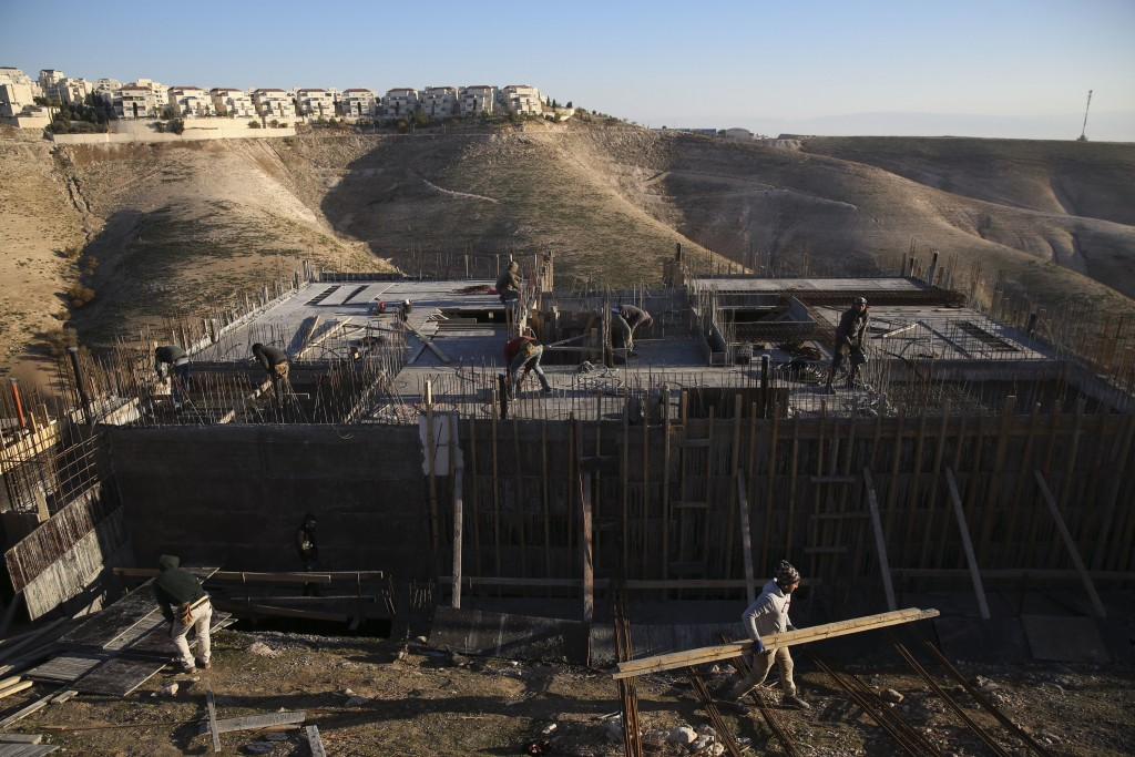 FILE - In this Feb. 7, 2017 file photo, Palestinian laborers work at a construction site in the Israeli settlement of Maale Adumim, near Jerusalem. Is...