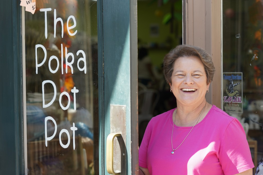 Polka Dot Pot owner Emily Rhodes poses at the front door of her shop In the Old Town area Wednesday Oct. 7, 2020, in Winchester, Va.   The viral pande...