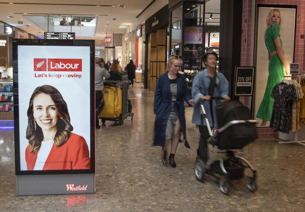 Shoppers walk past an electronic billboard showing a photo of New Zealand Prime Minister Jacinda Ardern in Christchurch, New Zealand, Wednesday, Oct. ...