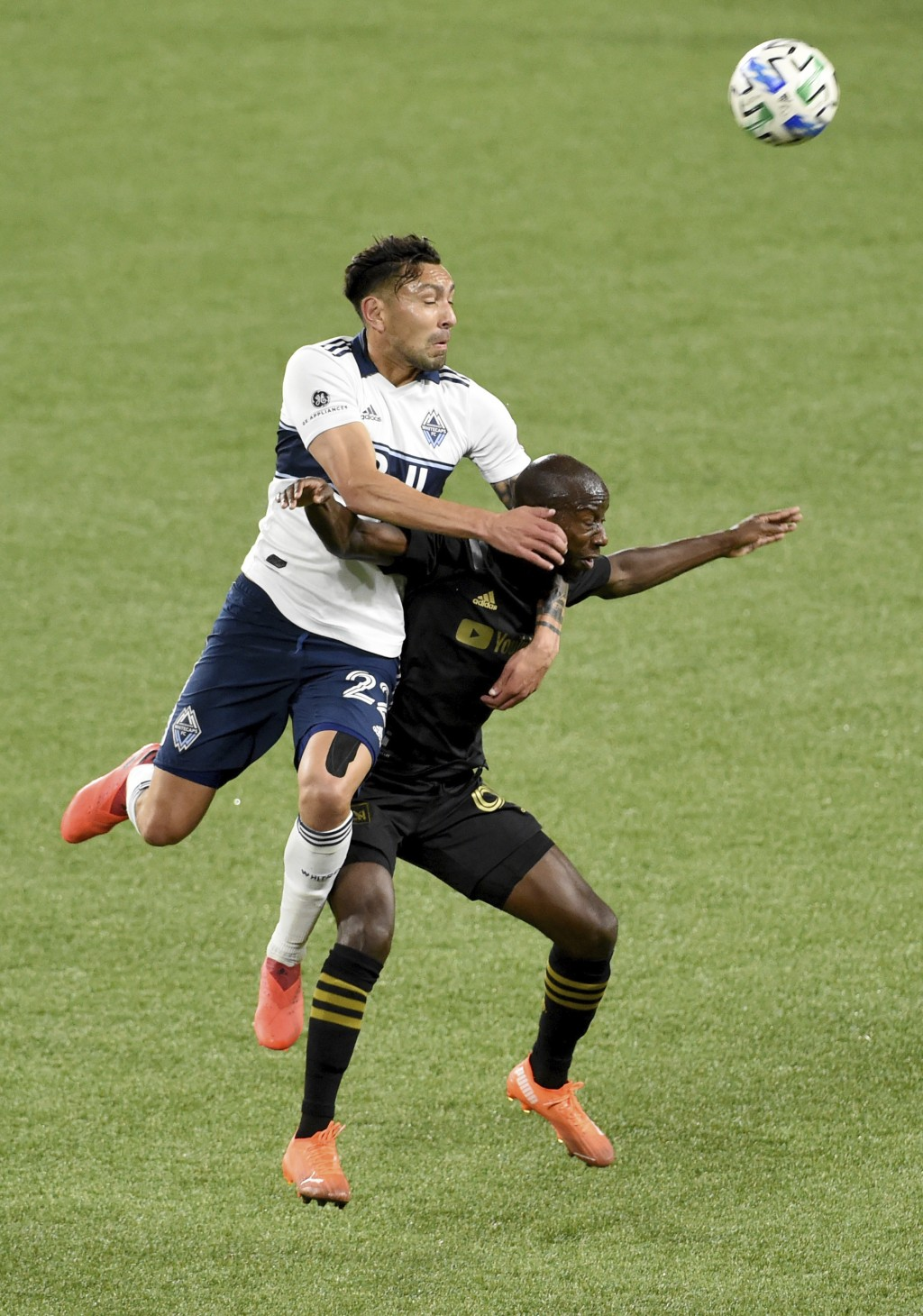 Vancouver Whitecaps defender Erik Godoy, left, and Los Angeles FC forward Bradley Wright-Phillips go up for a ball during the first half of an MLS soc...