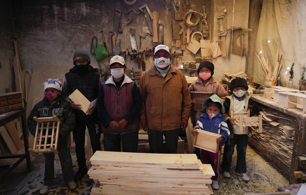 Wearing masks to curb the spread of the new coronavirus, the Delgado family poses for a photo in their carpentry workshop in El Alto, Bolivia, Friday,...