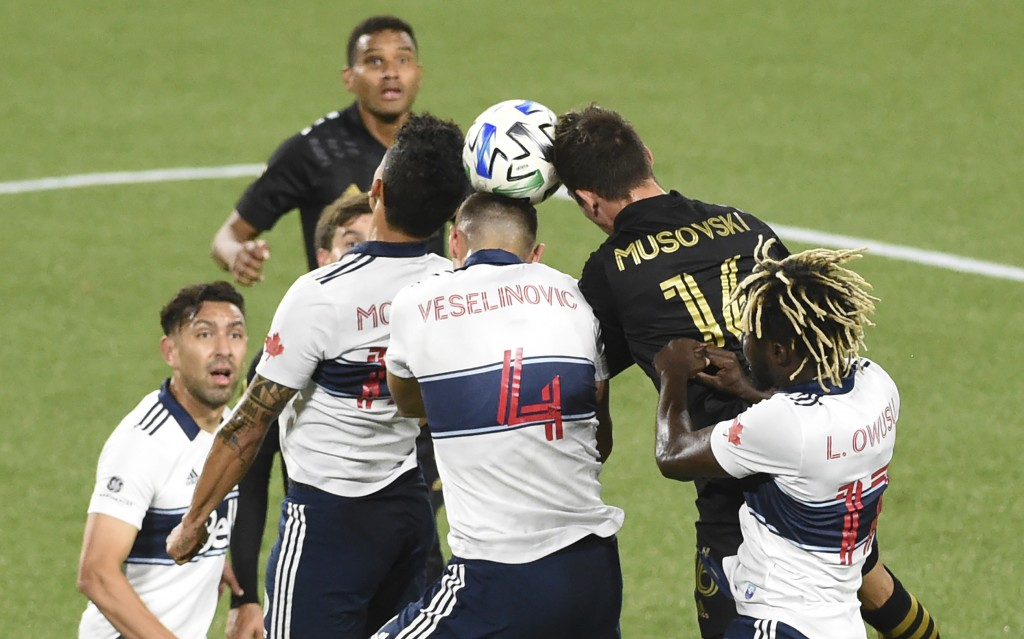 Los Angeles FC forward Danny Musovski, center, goes up for a ball in front of the goal with Vancouver Whitecaps midfielder Leonard Owusu, right, and d...