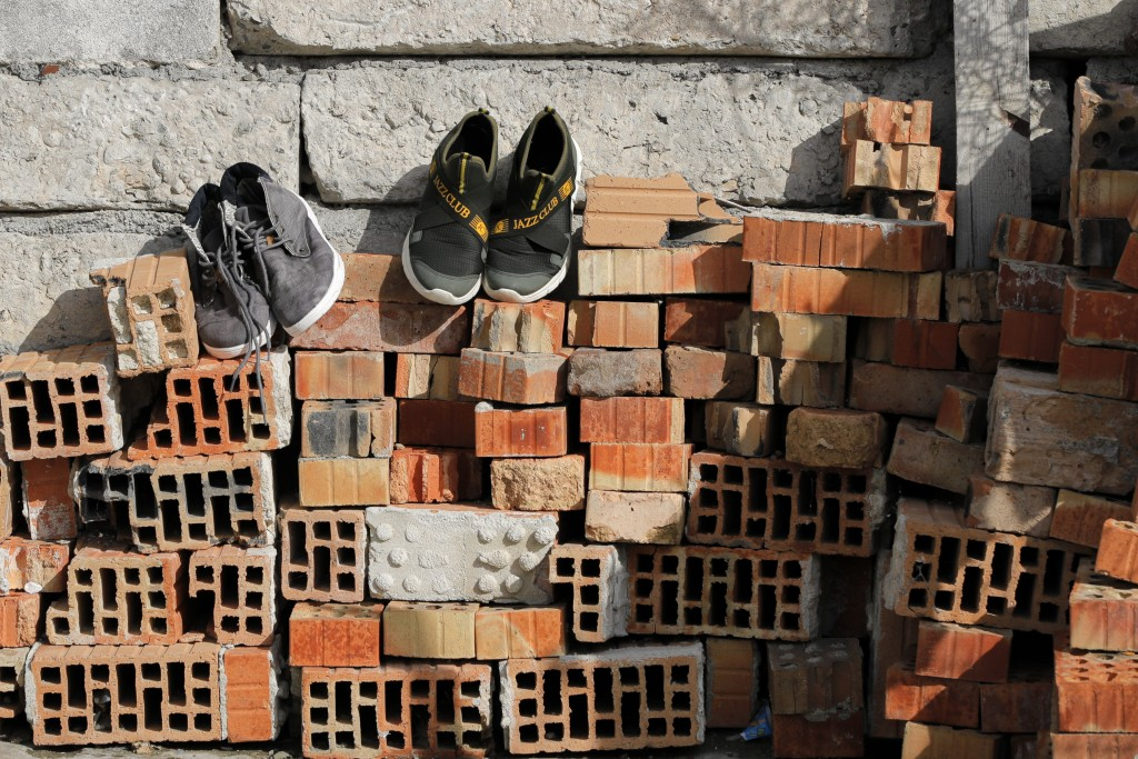 Shoes are placed on a pile of bricks to dry in the yard of the Topchu family house in a village on the outskirts of Burgas, Bulgaria, Monday, Sept. 28...