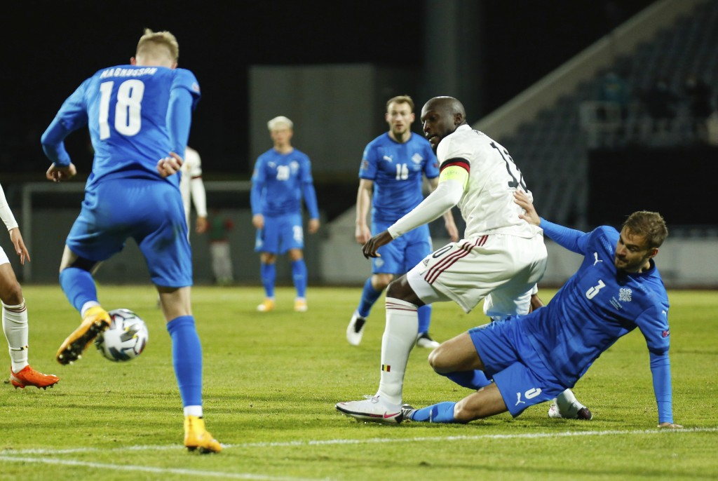 Iceland's Holmar Eyjolfsson, right, and Belgium's Romelu Lukaku, centre, battle for the ball during the UEFA Nations League soccer match between Icela...