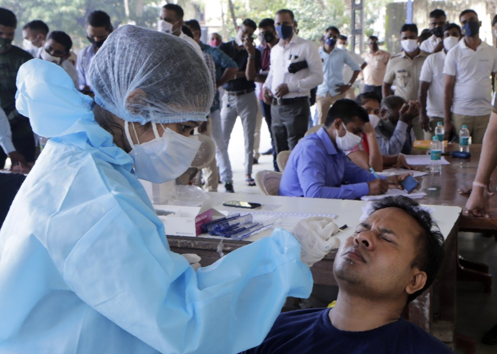 A health worker takes a nasal swab sample at a testing camp for COVID-19 for policemen in Mumbai, India, Thursday, Oct. 15, 2020. The southern state o...